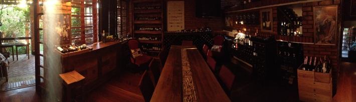 Sala principal da Vinho e Arte: vinhos escolhidos a dedo e uma mesa entre amigos