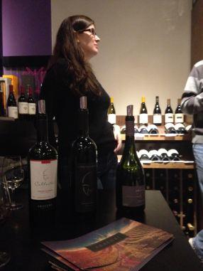 Paula e as garrafas abertas para degustação dos clientes na Sommelier Vinhos.
